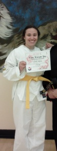 A disheveled me getting my yellow belt. Disheveled, but still victorious.